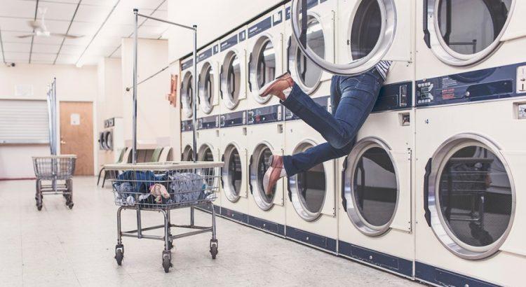 Person holt Wäsche aus der Waschmaschine